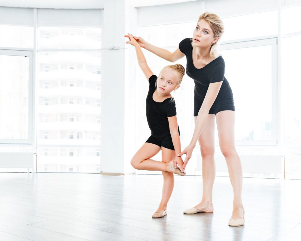 graphicstock-young-little-girl-ballerina-learning-dance-lesson-with-female-ballet-teac-SBI-302774989.jpg